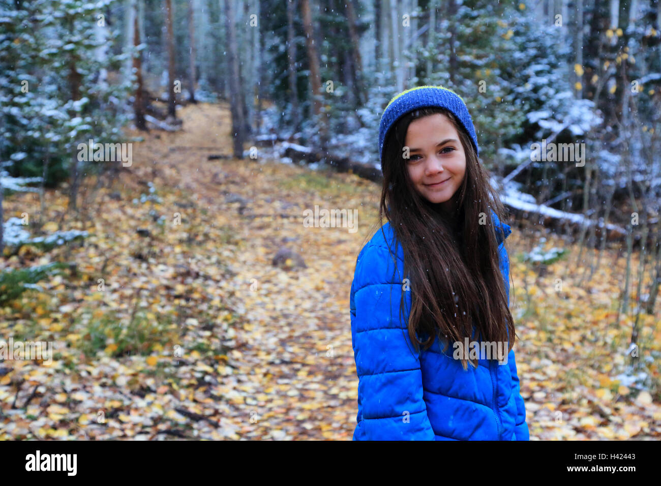 A brunette tween girl wearing winter clothing hikes in the woods. She is wearing a blue hat and a blue coat and - Stock Image