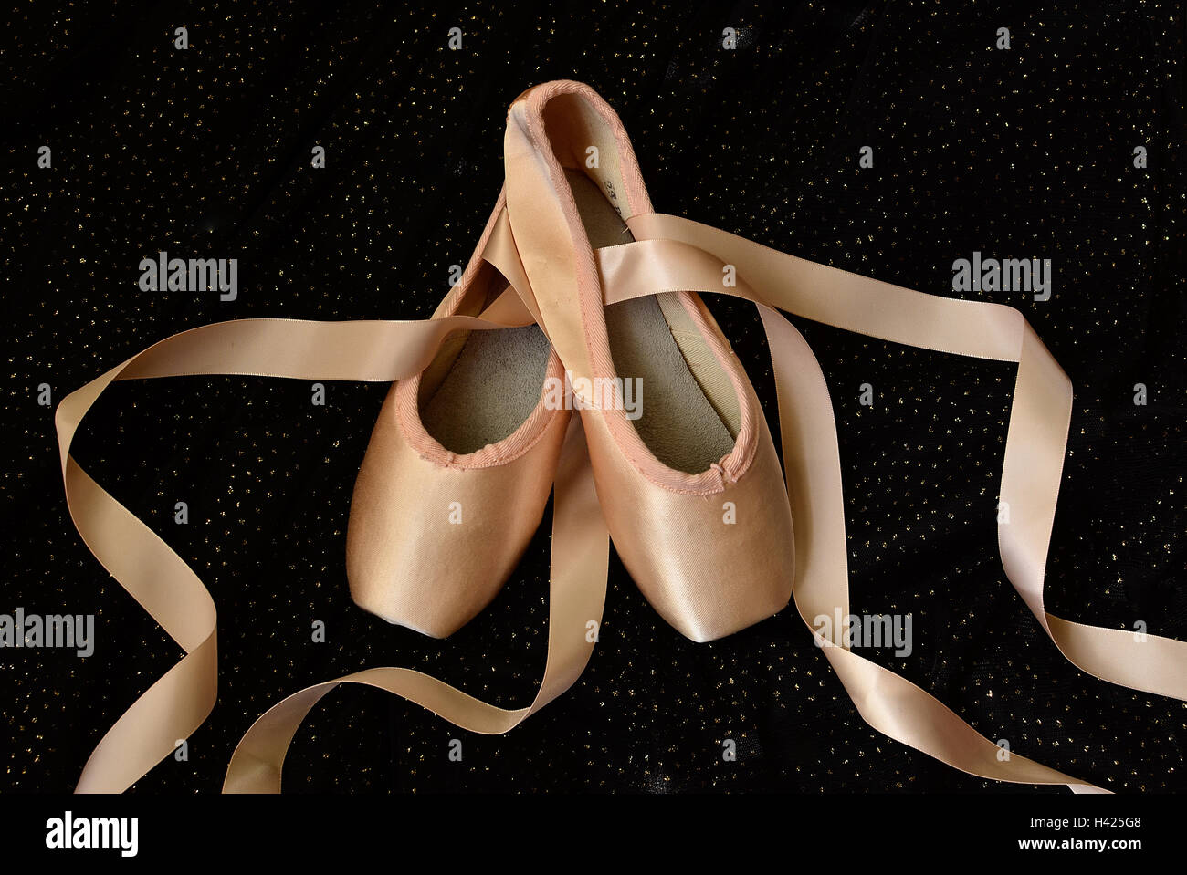 A pair of ballet shoes on  sparkling black background - Stock Image