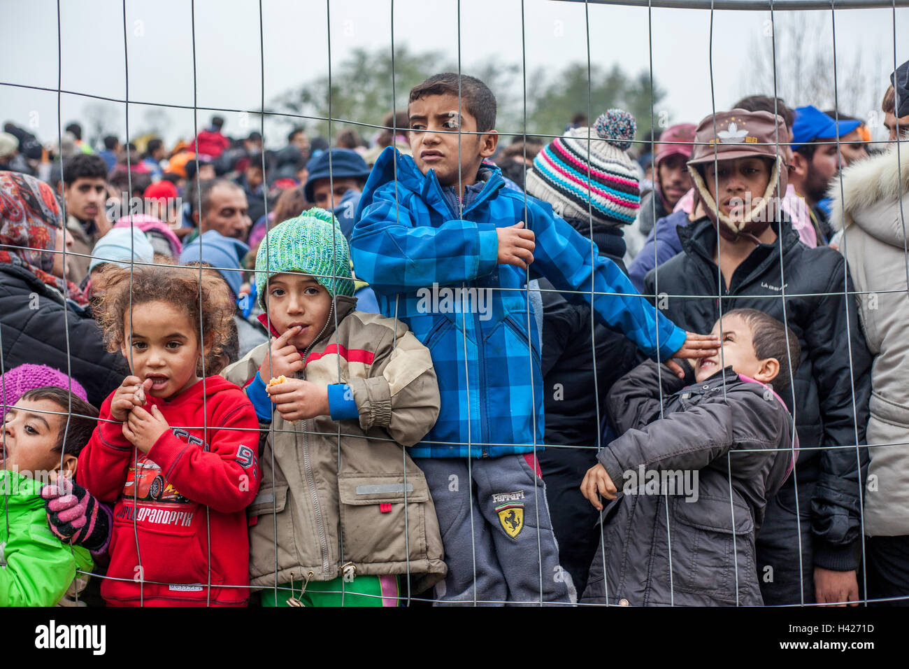 Children behind the fence waiting to cross the Slovenian-Austrian border in the refugee camp in Spielfeld. - Stock Image