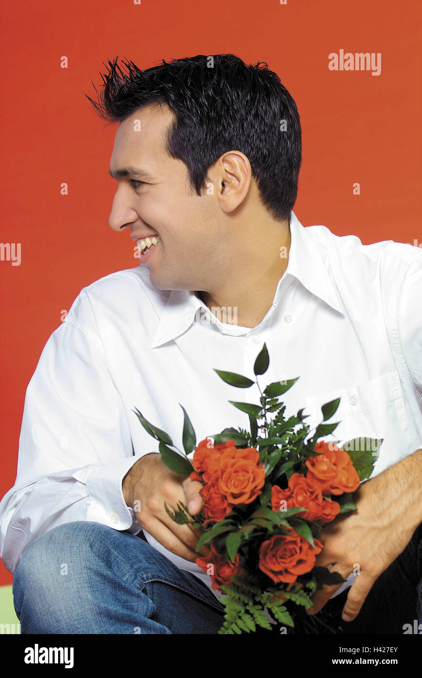 Man gaze at the side smiles crouch rose bouquet holds portrait man gaze at the side smiles crouch rose bouquet holds portrait mens portrait 20 30 years shirt white friendly happily bouquet flower bouquet izmirmasajfo