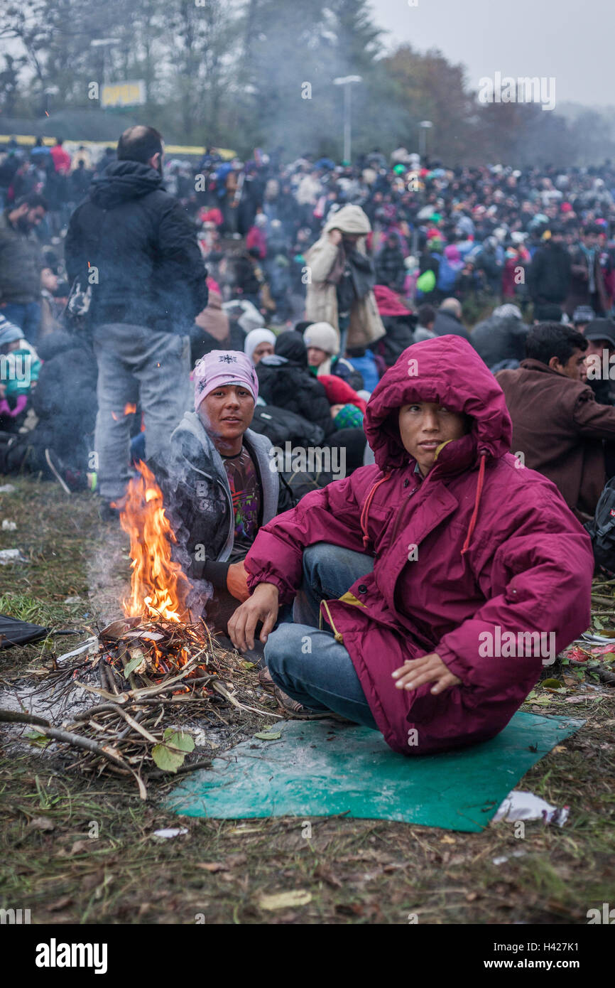 Refugees sitting next to campfire to warm up in the late autumn in the refugee camp on the border in Spielfeld, - Stock Image