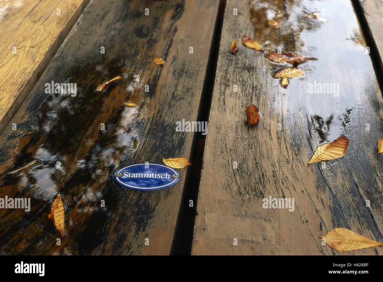 Beer garden, wood table, wet, detail,  Sign, group of regulars, fall foliage,   Table, wood surface, wood, sign, - Stock Image