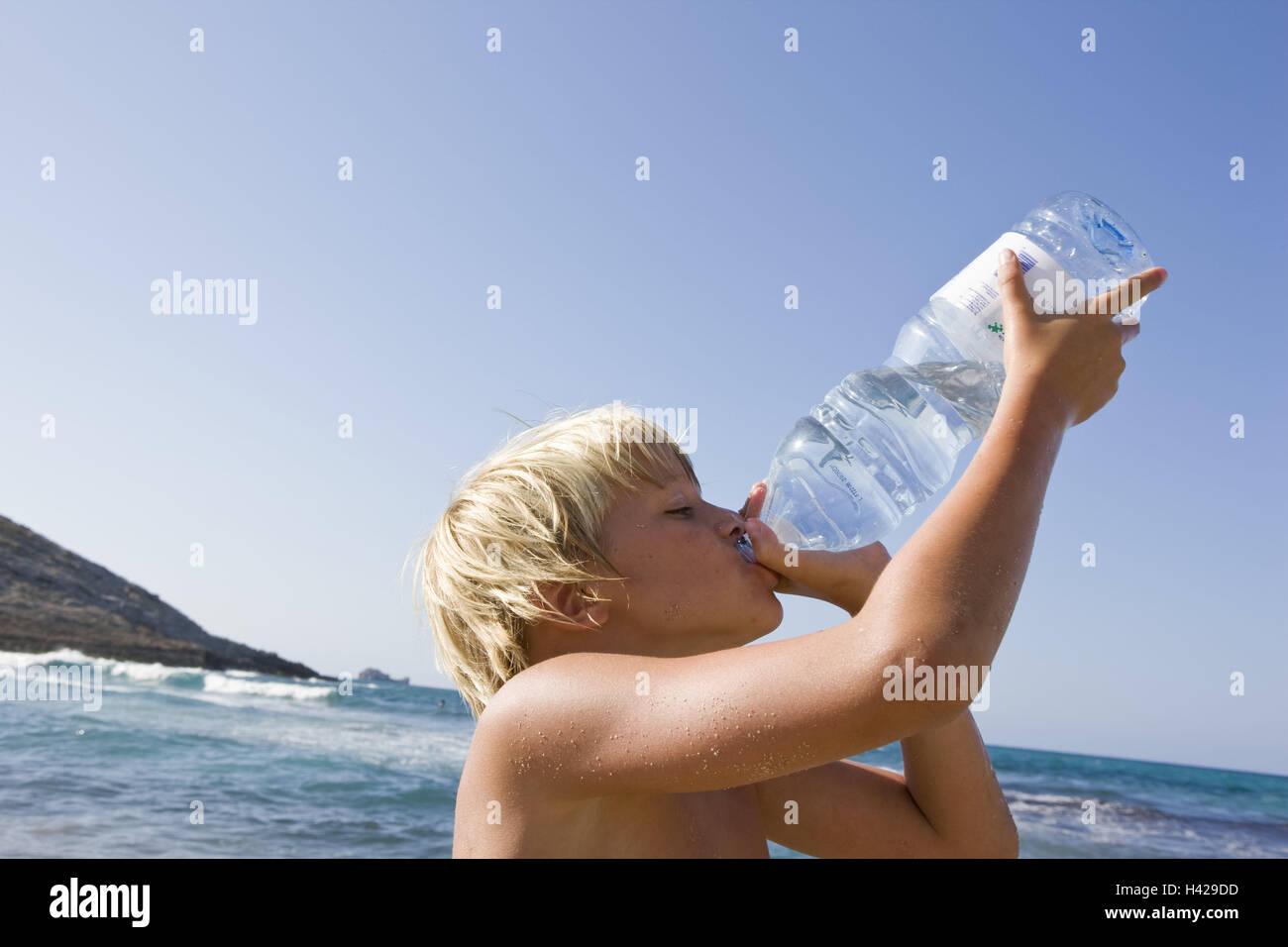 Beach, boy, thirsty, water bottle, drinking, portrait, side view, people, children, blond, summer holidays, holidays, - Stock Image