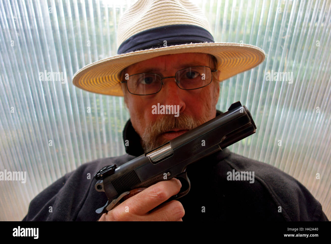 A criminal gang member gangster robber or mugger pointing a colt 45 automatic pistol - Stock Image