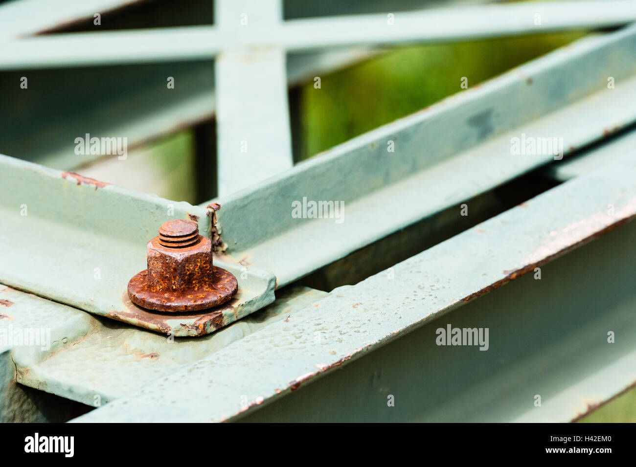 Detail of rusted hexagonal metal screw fastener on corner of painted steel bars and plates. Stock Photo
