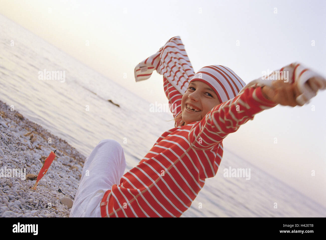 Beach, girls, cheerfully, liveliness   Child, 7 years, Shirt, roved, cap, headgear, sits, turns, gaze shoulder, - Stock Image