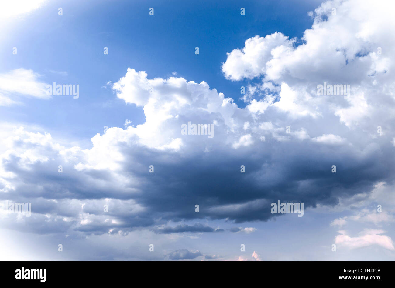 Large storm clouds on a bright sunny spring day - Stock Image
