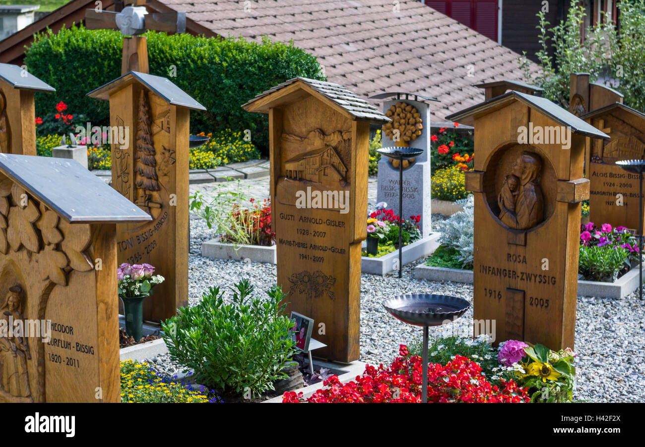 Graves with carved wooden tombstones at the cemetery of Isenthal, a village in the Swiss Alps. Canton of Uri, Switzerland. - Stock Image