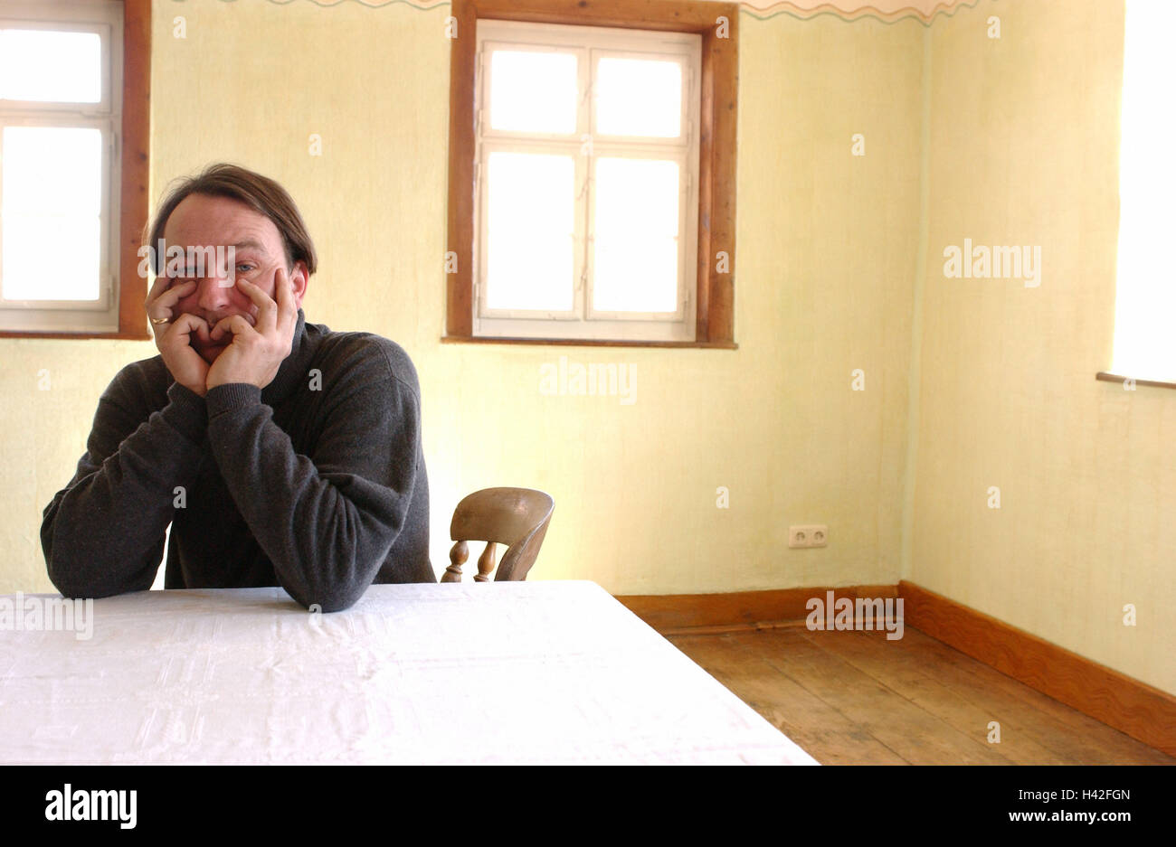 Living space, sit blank, table, man, head rest on, sadly, portrait, Ti5, flat, old building, exited, 30-40 years, - Stock Image