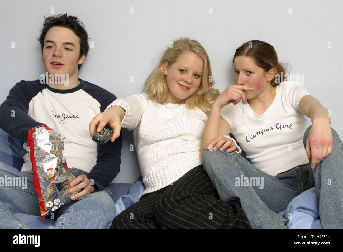 Teenagers, boy, girl, watch TV, zap, eat crisps, happy, only positive use 17 years, young persons, teenagers, three, - Stock Image