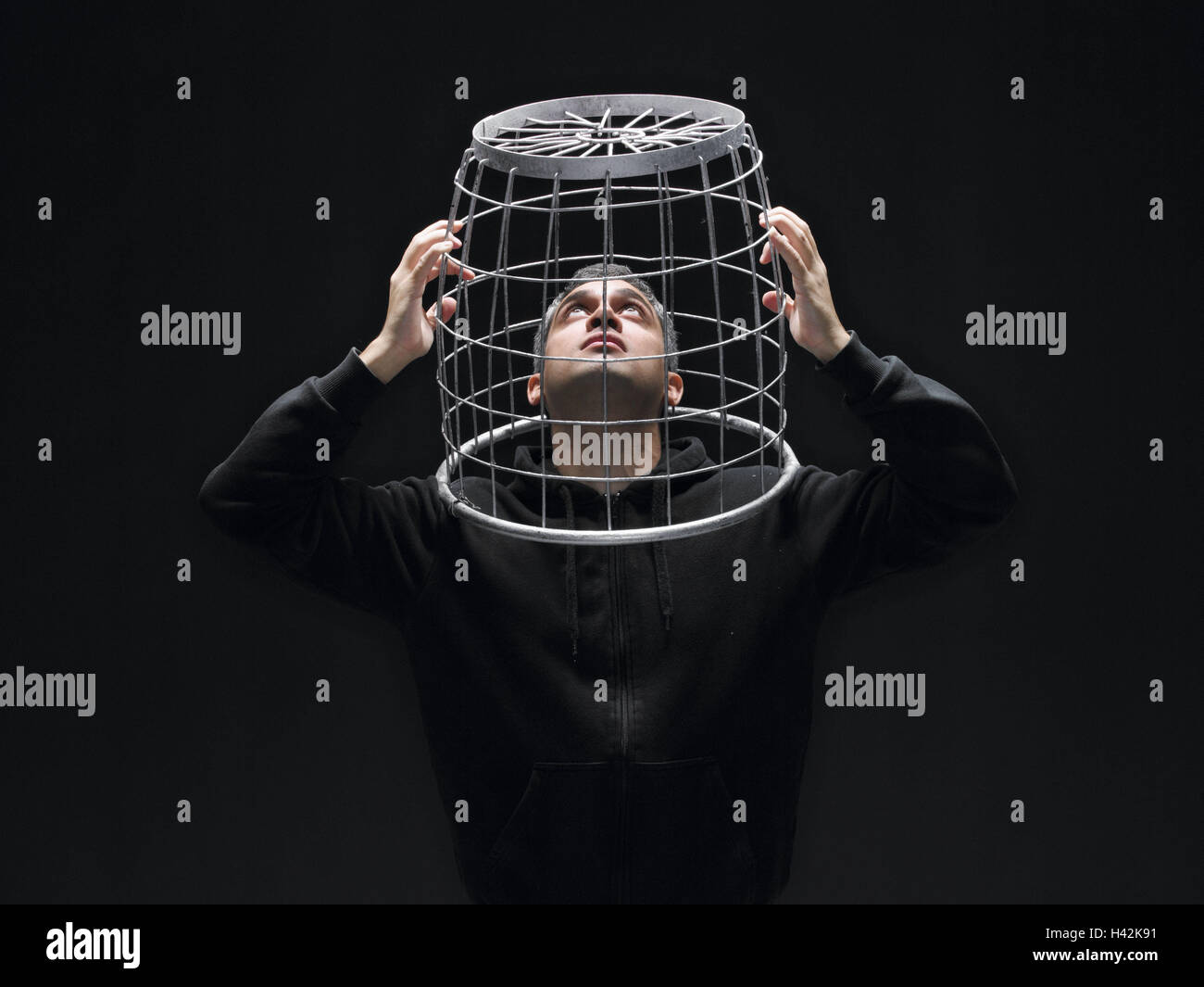 Man, 'card cage', caught, desperation, hopelessness, portrait, grid, basket, head, thought, not free, locked - Stock Image