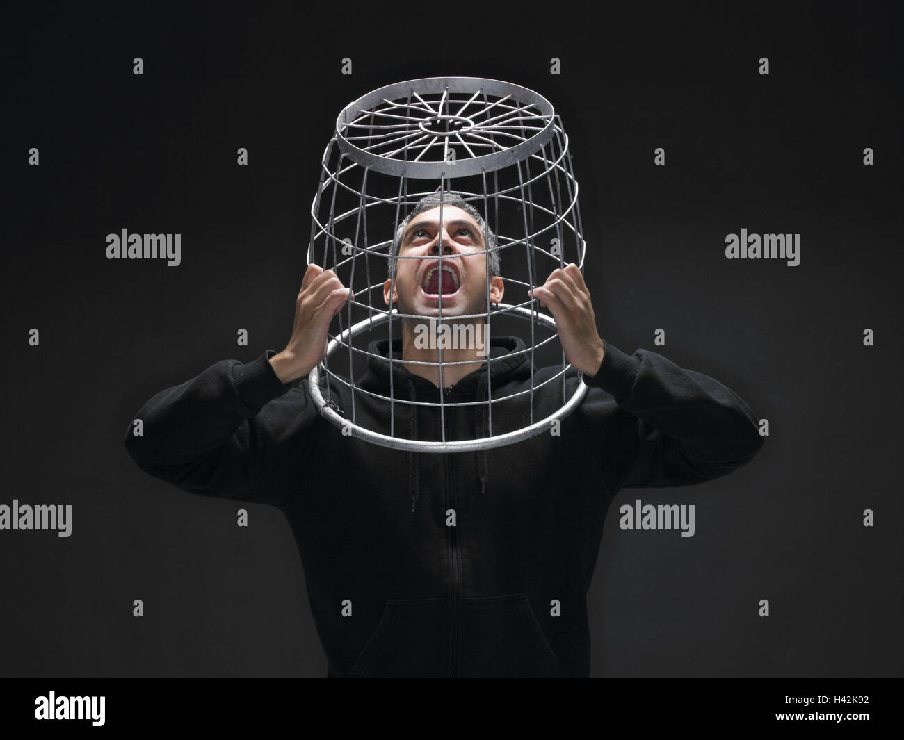 Man, 'card cage', caught, desperation, hopelessness, shout, portrait, grid, basket, head, thought, not free, - Stock Image