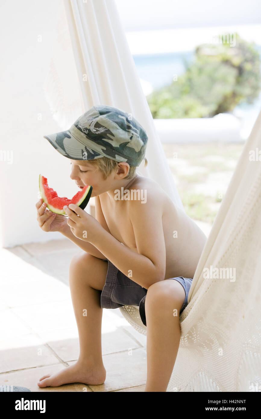 Boy, watermelon, eating, barechested, cap, sitting, hammock, model released, - Stock Image