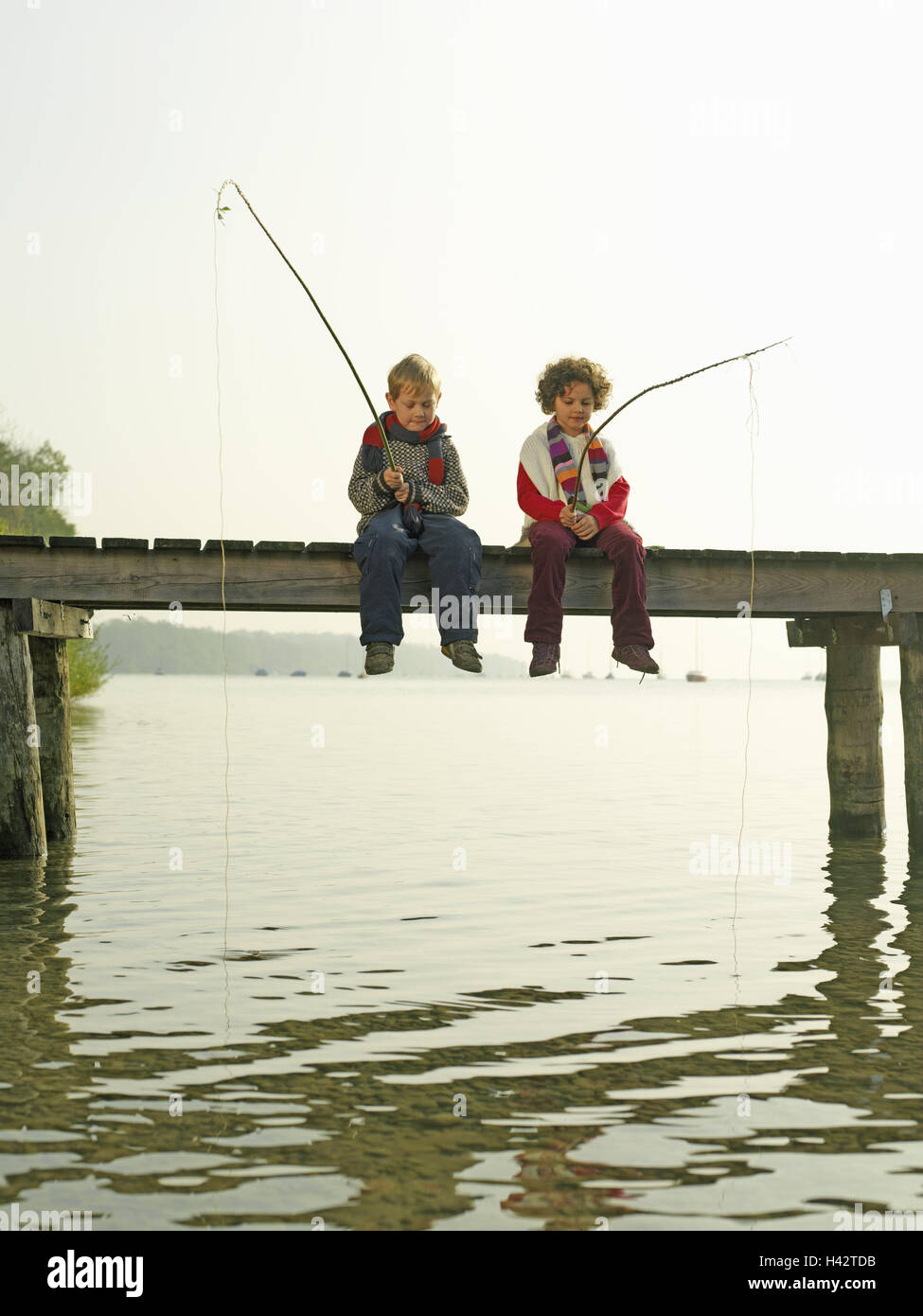 Lakes, bridge, children, girls, boy, sit, fish, wait, autumn, waters, wooden jetty, water, leisure time, holidays, - Stock Image