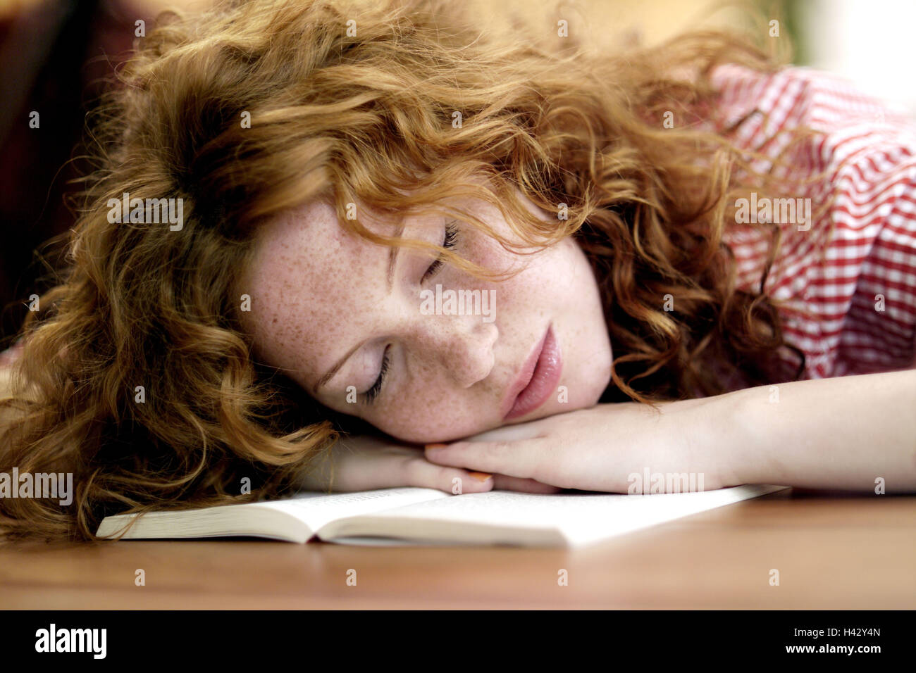 Table, detail, woman, young, book, head, hang up, sleep, portrait, redheads, red-haired, long-haired, curls, leisure - Stock Image