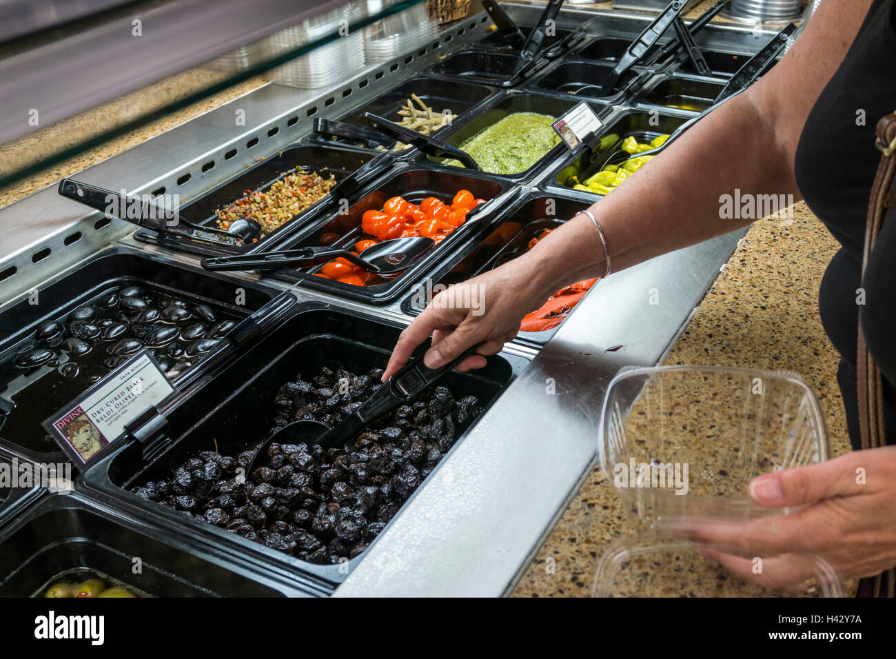 Woman selecting dry-cured black Beldi olives from a supermarket self-service delicatessen counter. Stock Photo