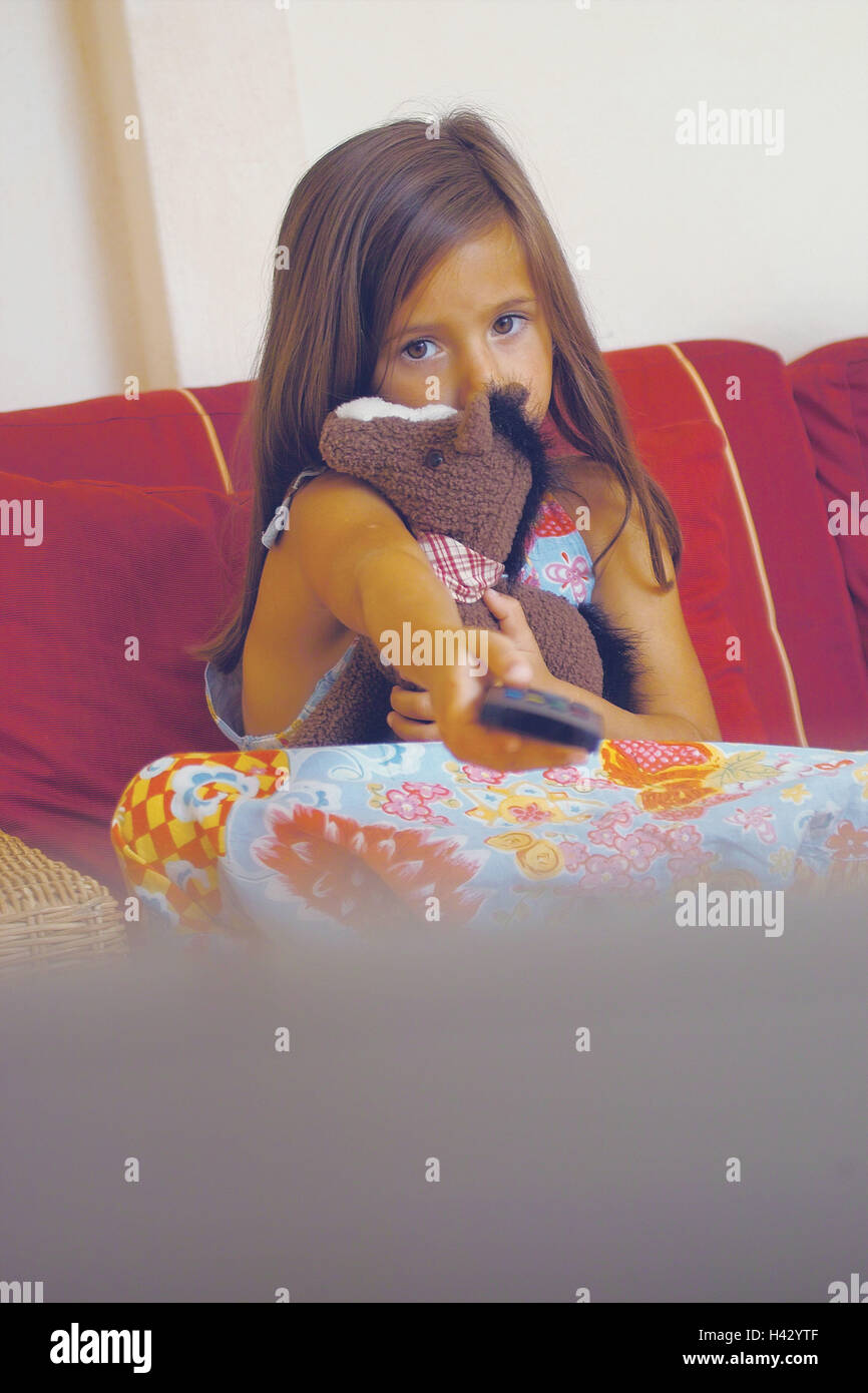 Sofa, girl, soft toy, remote control, zap, 6 years, child, at home, couch, take it easy, sit, only, expression, - Stock Image