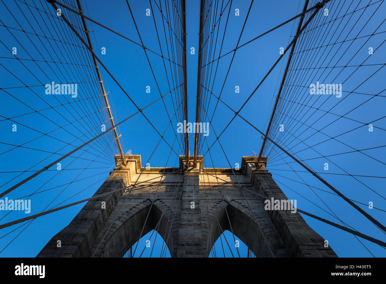 Symmetry of steel wire rope cables of the Brooklyn Bridge with a clear blue sky and last rays of sun. New York City - Stock Image