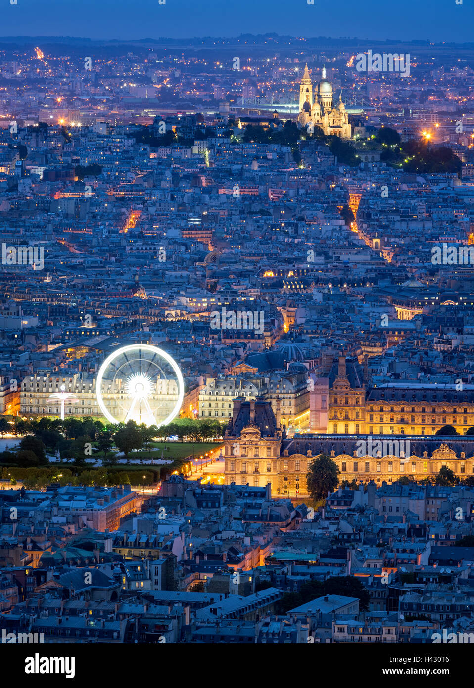 Aerial view of Paris rooftops at dusk, including The Louvre, and Sacre Coeur in Montmartre. Blue hour in the City Stock Photo