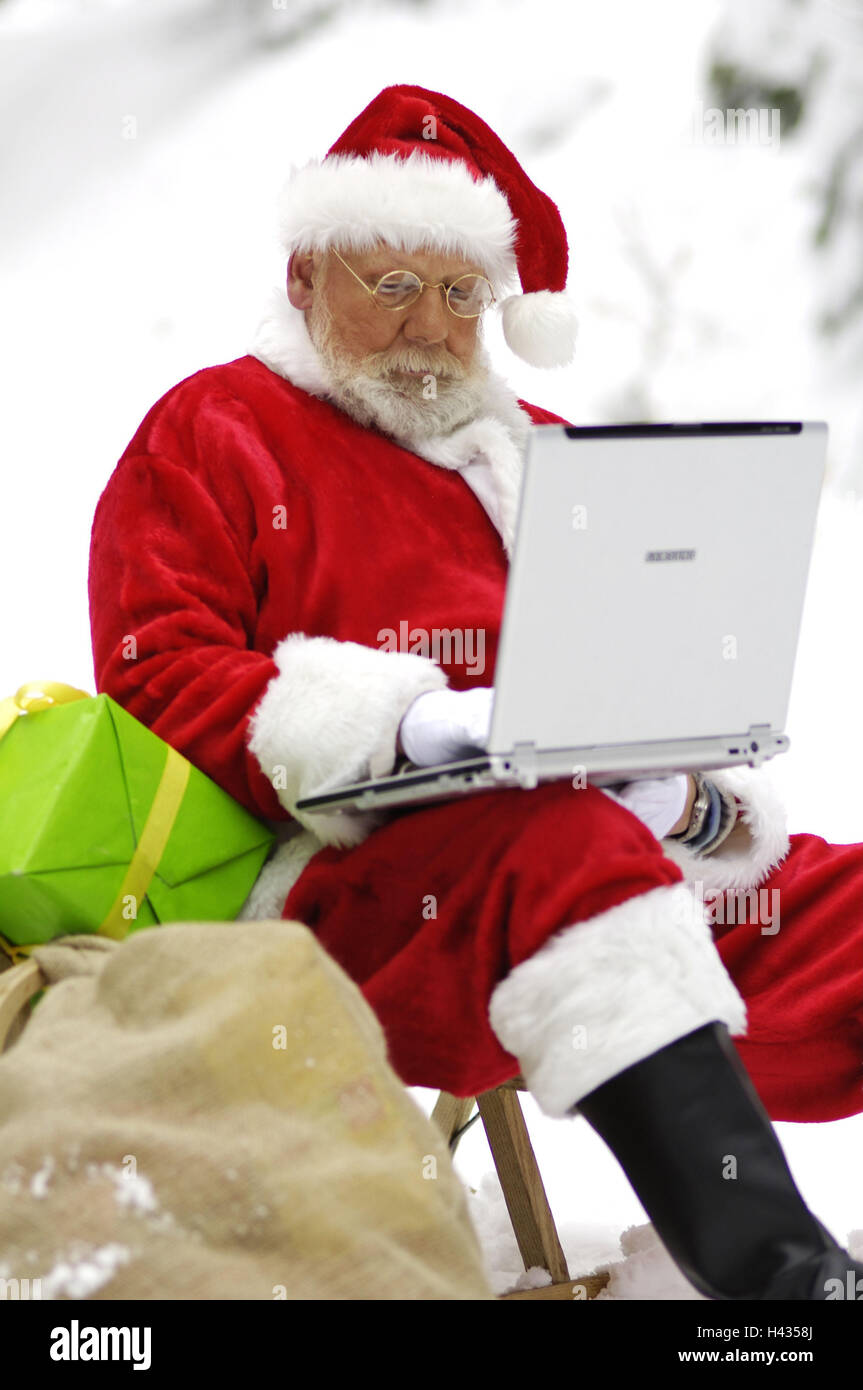 Santa Claus, slide, sit, presents, notebook computer, data request, winter, Christmas, person, man, modern, deliver Stock Photo