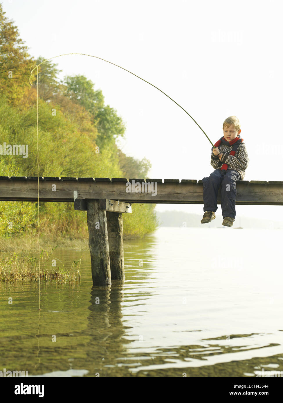 Lakes, bridge, child, boy, sit, fish, wait, autumn, waters, wooden jetty, water, leisure time, holidays, autumn - Stock Image
