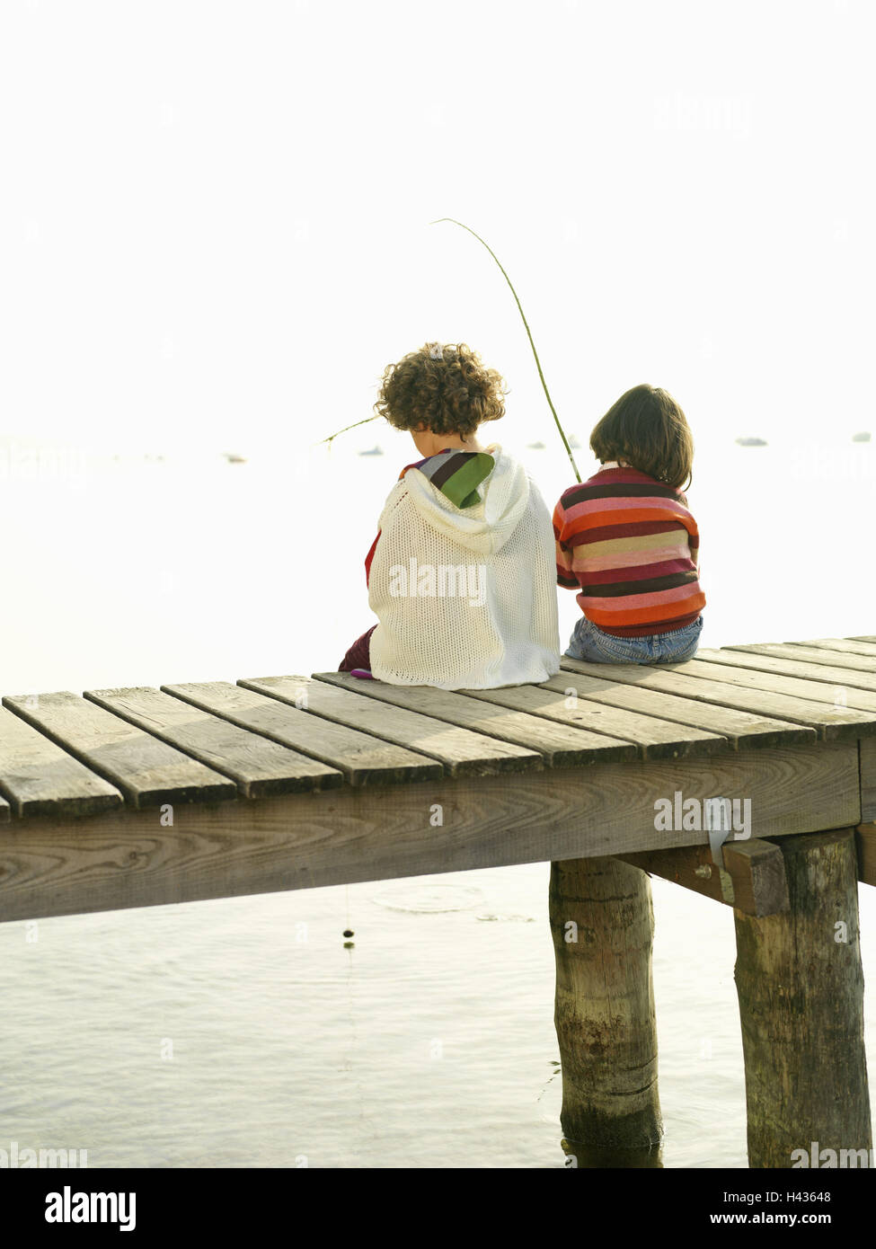 Lakes, bridge, children, girls, sit, fish side by side, back view, waters, wooden jetty, water, leisure time, holidays, - Stock Image