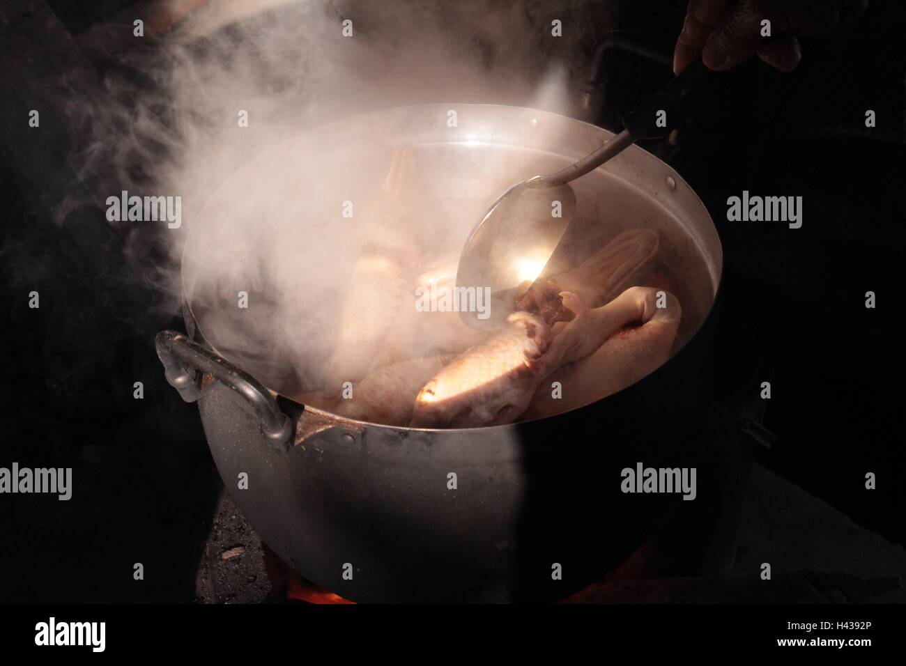 Old pot of food cooking on burning wood fire stove - Stock Image