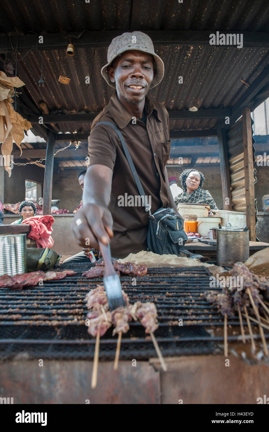 Seller grilling meat at street stand, street scene, Bamenda, North-West Region, Cameroon - Stock Image