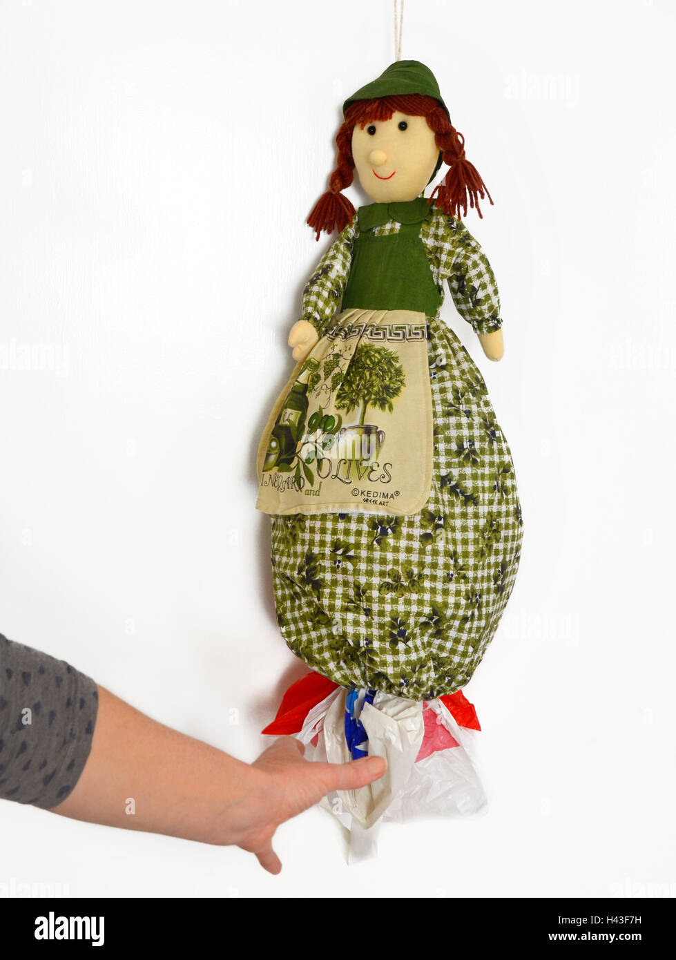 A dollie bag holder/ dispenser of plastic bags. A person reaches out to take one out. - Stock Image