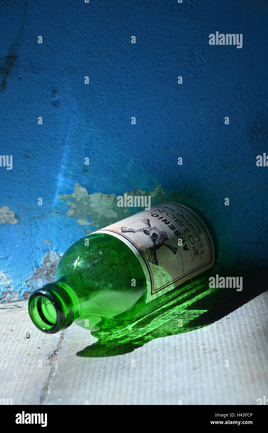 An old green glass  bottle labelled with arsenic poison and a skull and bone sign lies on the ground. - Stock Image