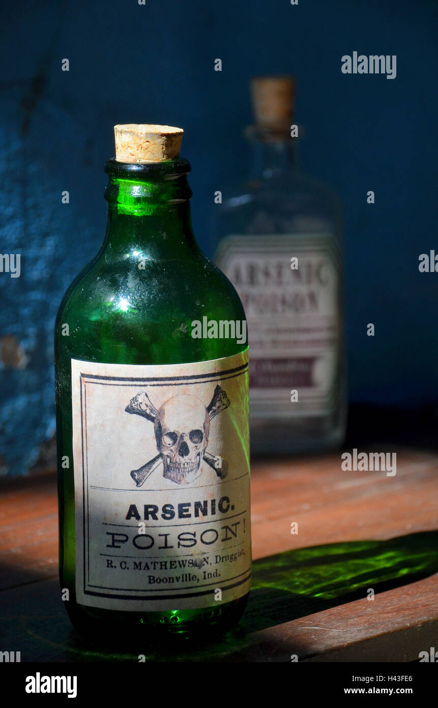 old green glass bottle labelled with arsenic poison and  skull and bones stands on a shelf. Another poison bottle - Stock Image