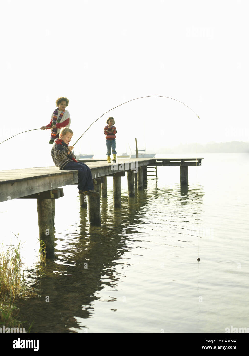 Lakes, bridge, children, girls, stand, boy, sit, fish, wait, autumn, waters, wooden jetty, water, leisure time, - Stock Image