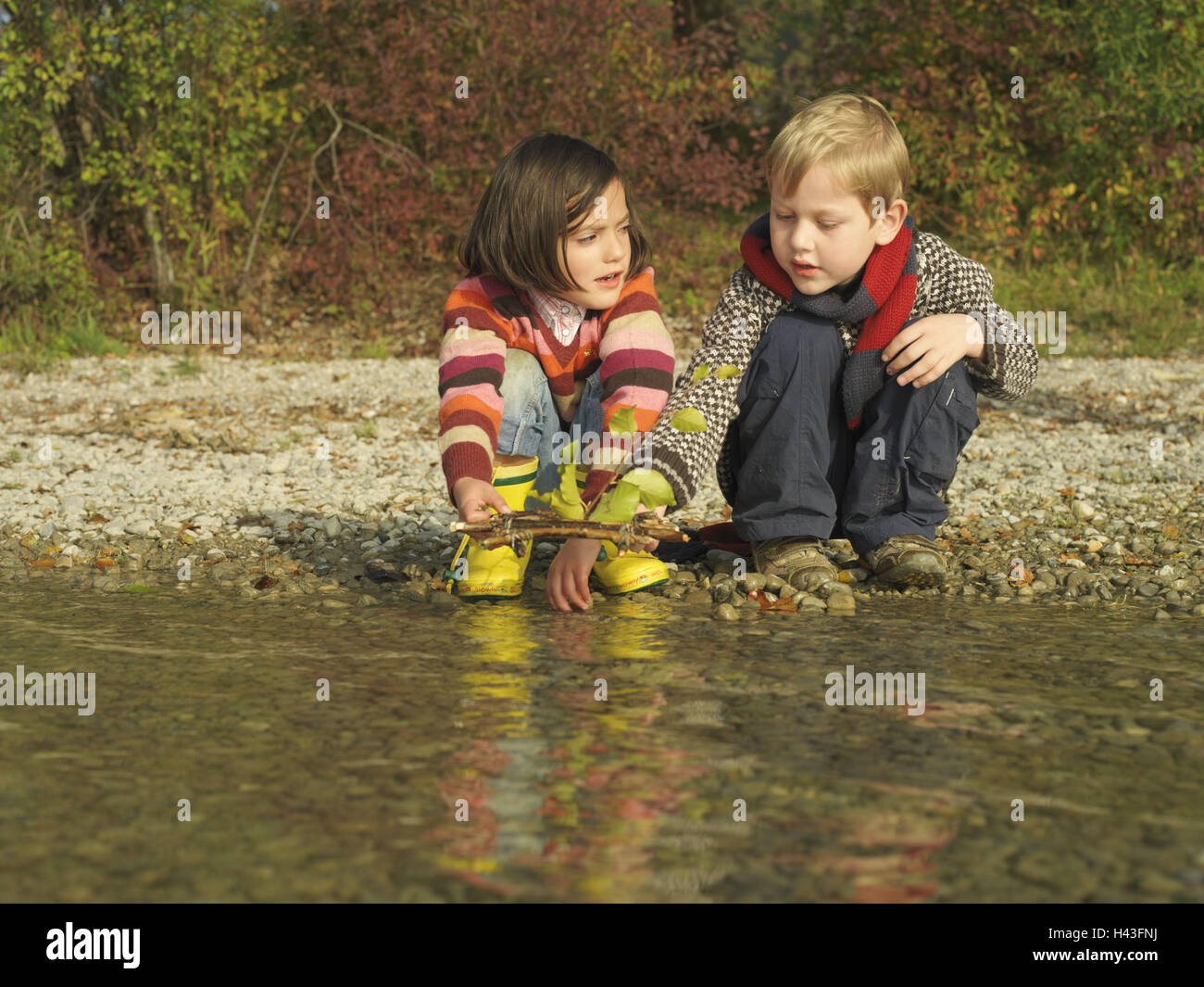 Lakesides, children, girls, boy, crouch, play, raft, selfbuilt, try out, autumn, waters, lake, shore, water, leisure - Stock Image