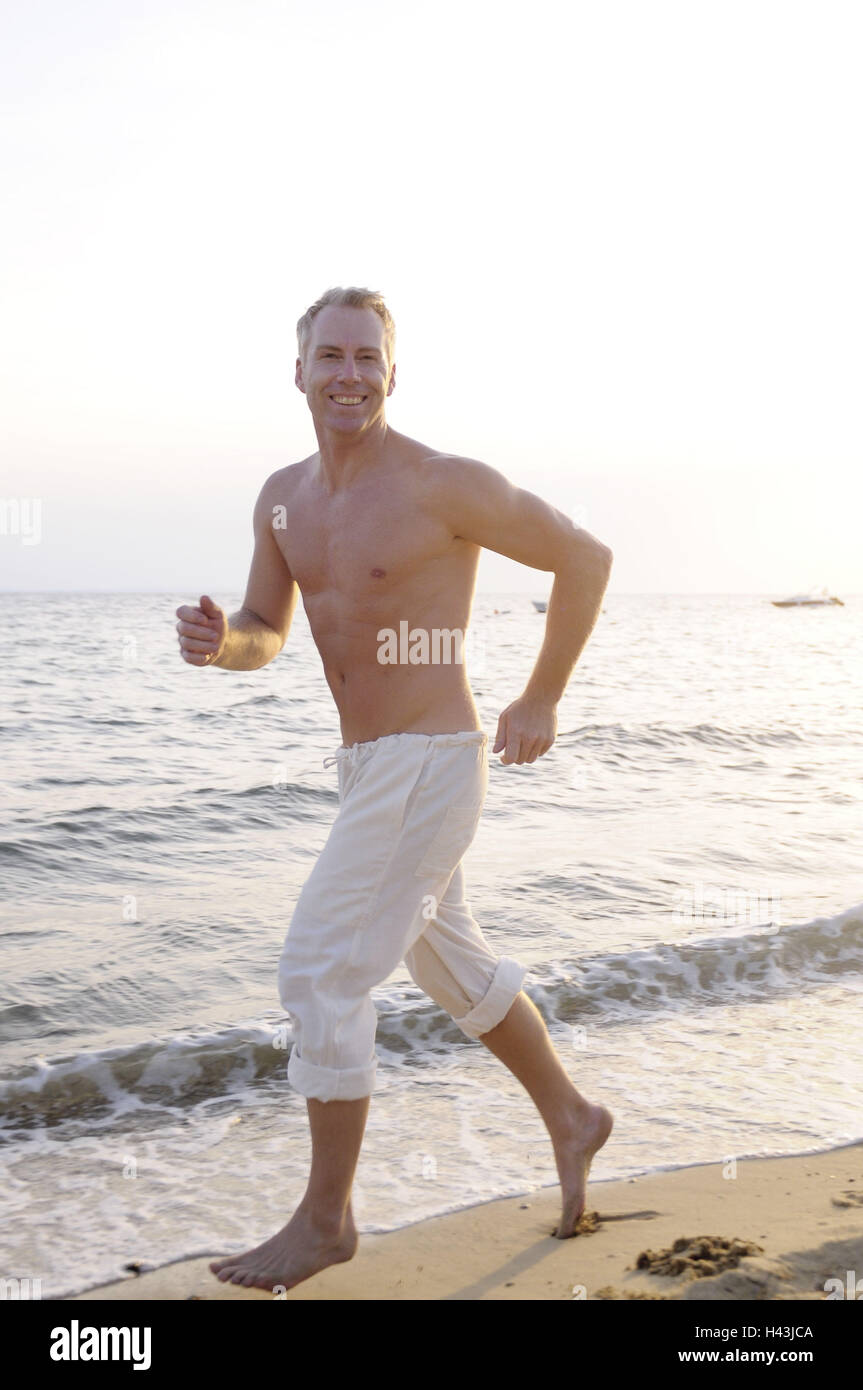 Man, middle old person, free upper part of the body, beach, jog, model released, - Stock Image