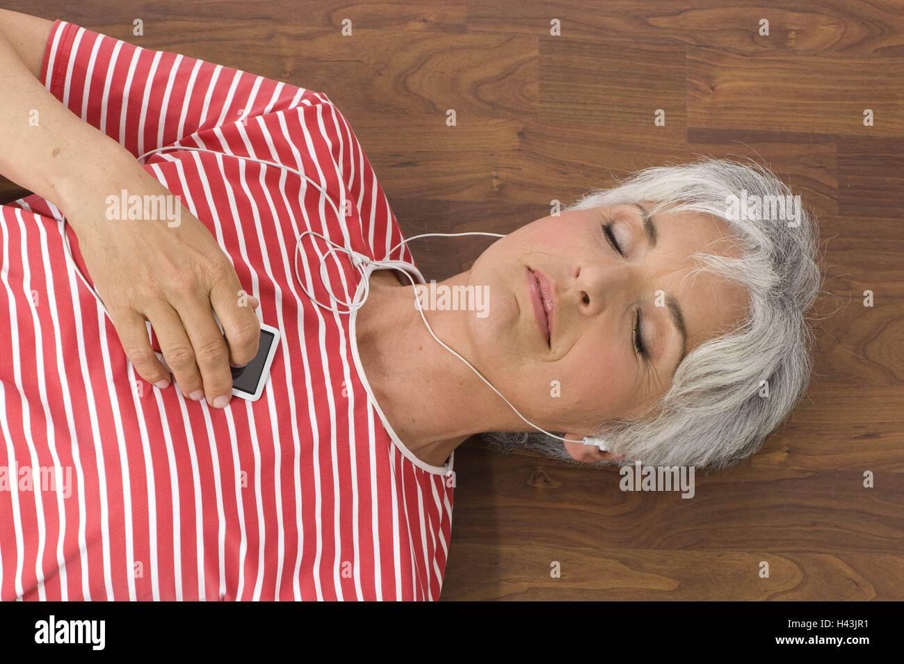 Senior, floor, lie, earphones, recreation, portrait, from above, people, senior citizens, woman, lifestyle, cultivated, - Stock Image