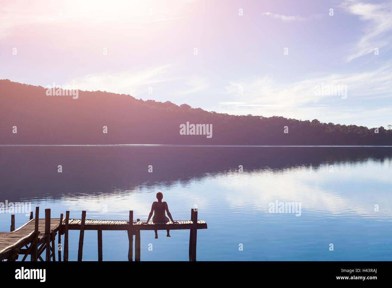 Happy woman sitting on a pier and getting inspired by the beautiful nature - Stock Image