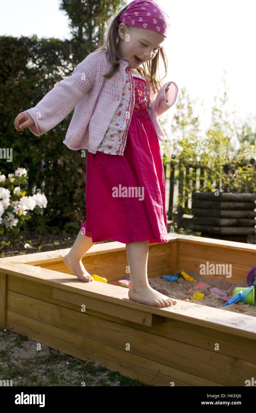 Girls, balance, sandbox, garden, summer, evening light, - Stock Image