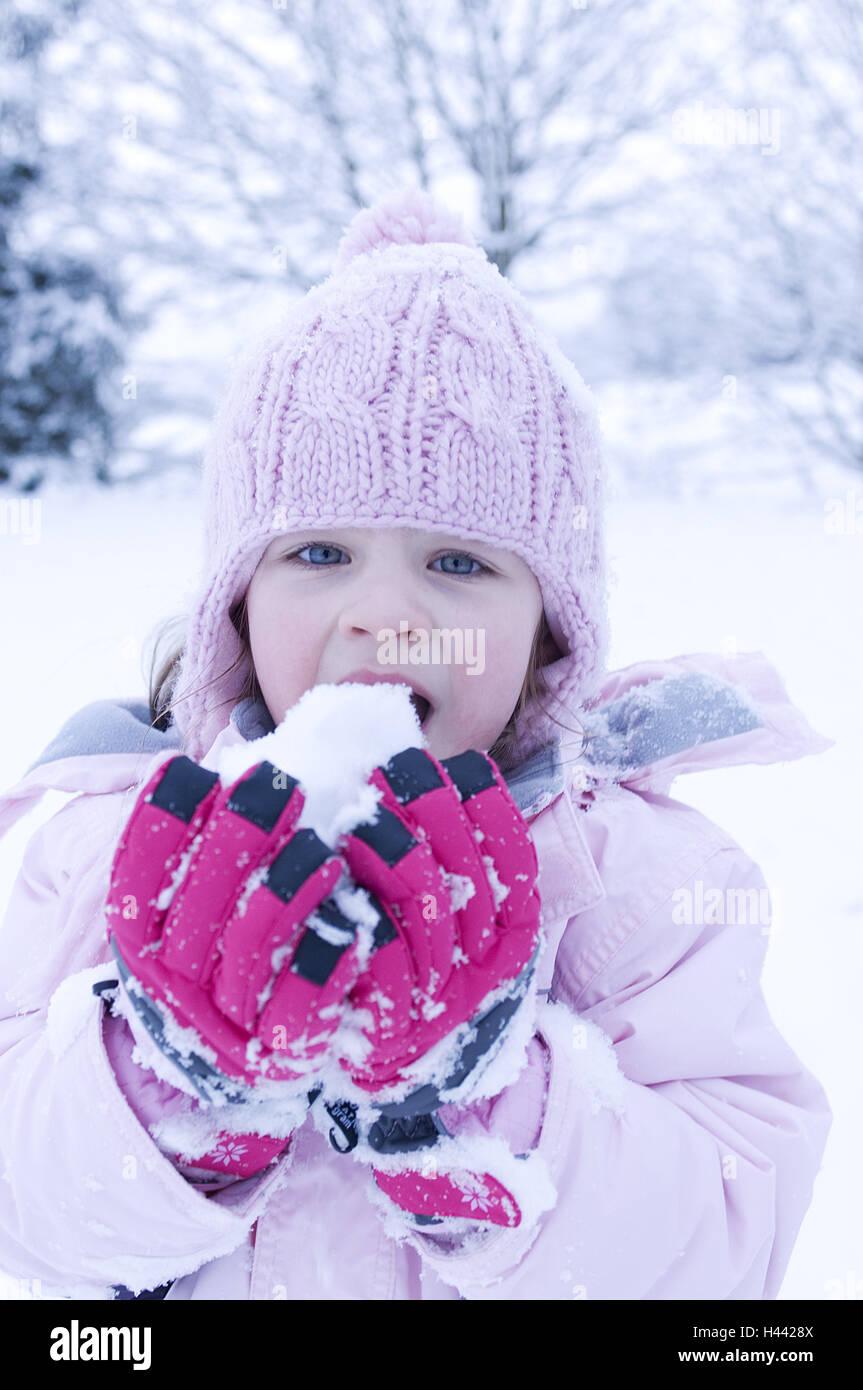 Girl, winter clothes, cap, snowball, - Stock Image
