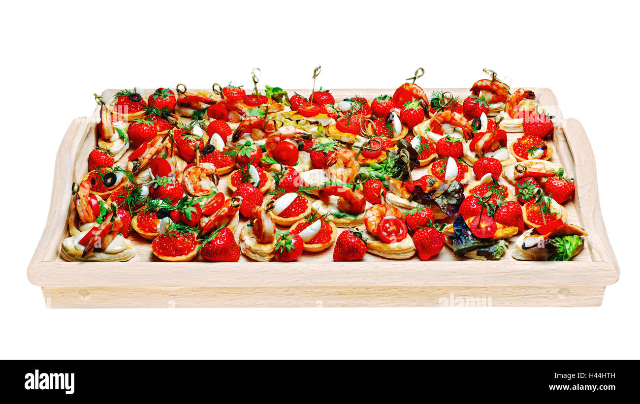 Lot of canape with shrimp, caviar, strawberries and other on wooden tray isolated on white background - Stock Image