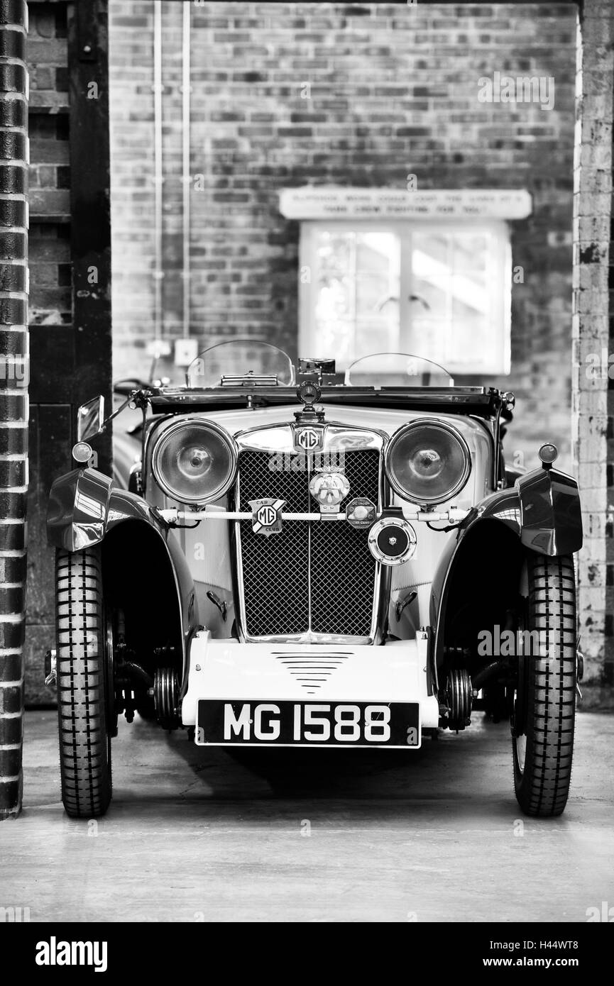 1932 MG car in a workshop at Bicester Heritage Centre. Oxfordshire, England. Black and White - Stock Image