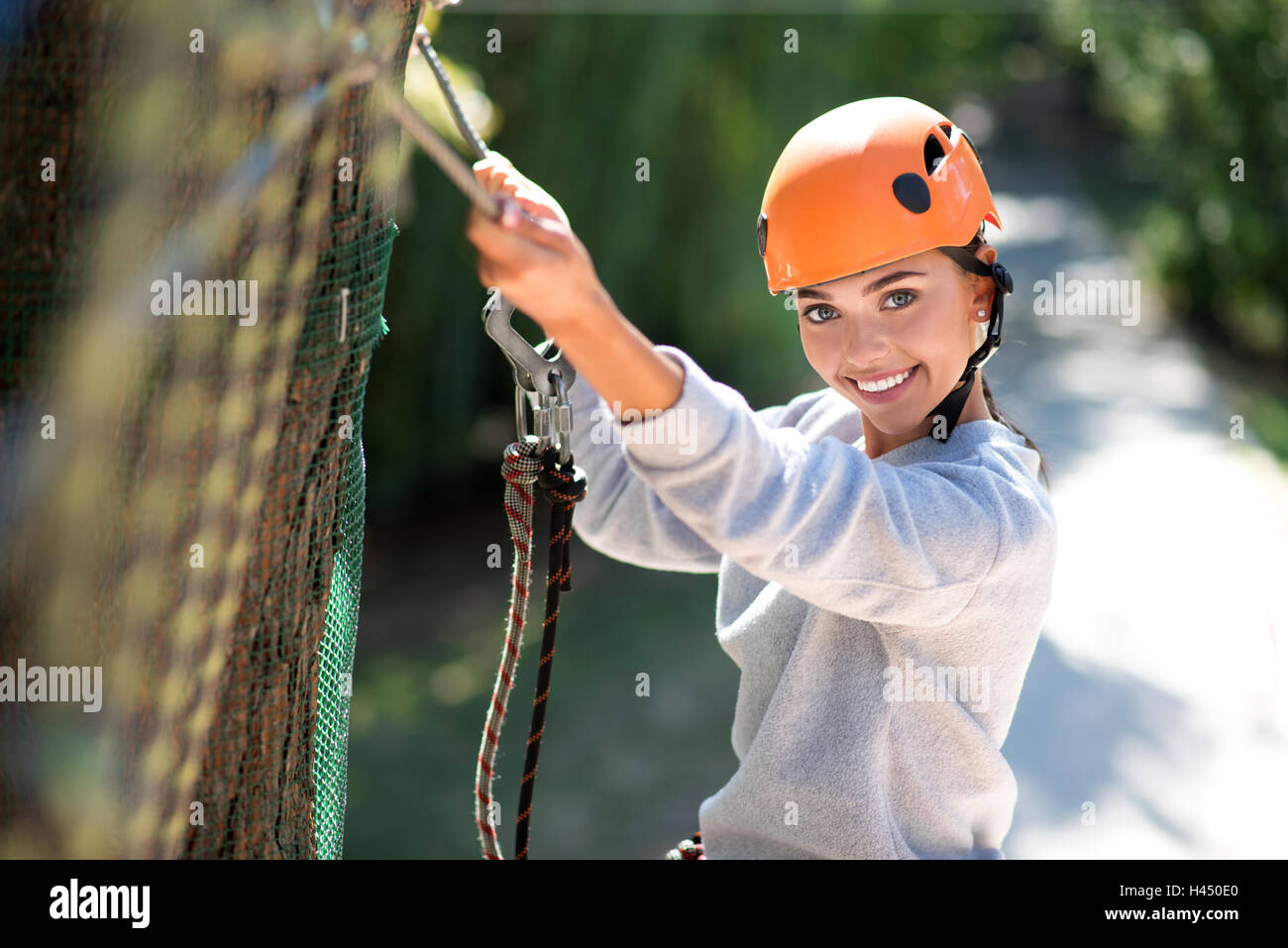 Brave enthusiastic woman clambering in the rope park - Stock Image