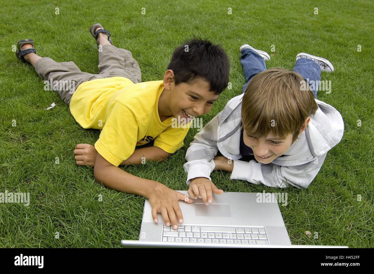 Boys, two, turfs, lie, play laptop, fun, model released, people, children, friends, learn, outside, meadow, park, - Stock Image