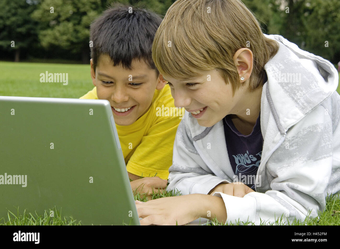 Boys, two, turfs, lie, play laptop, fun, model released, people, children, friends, learn, outside, together, meadow, - Stock Image