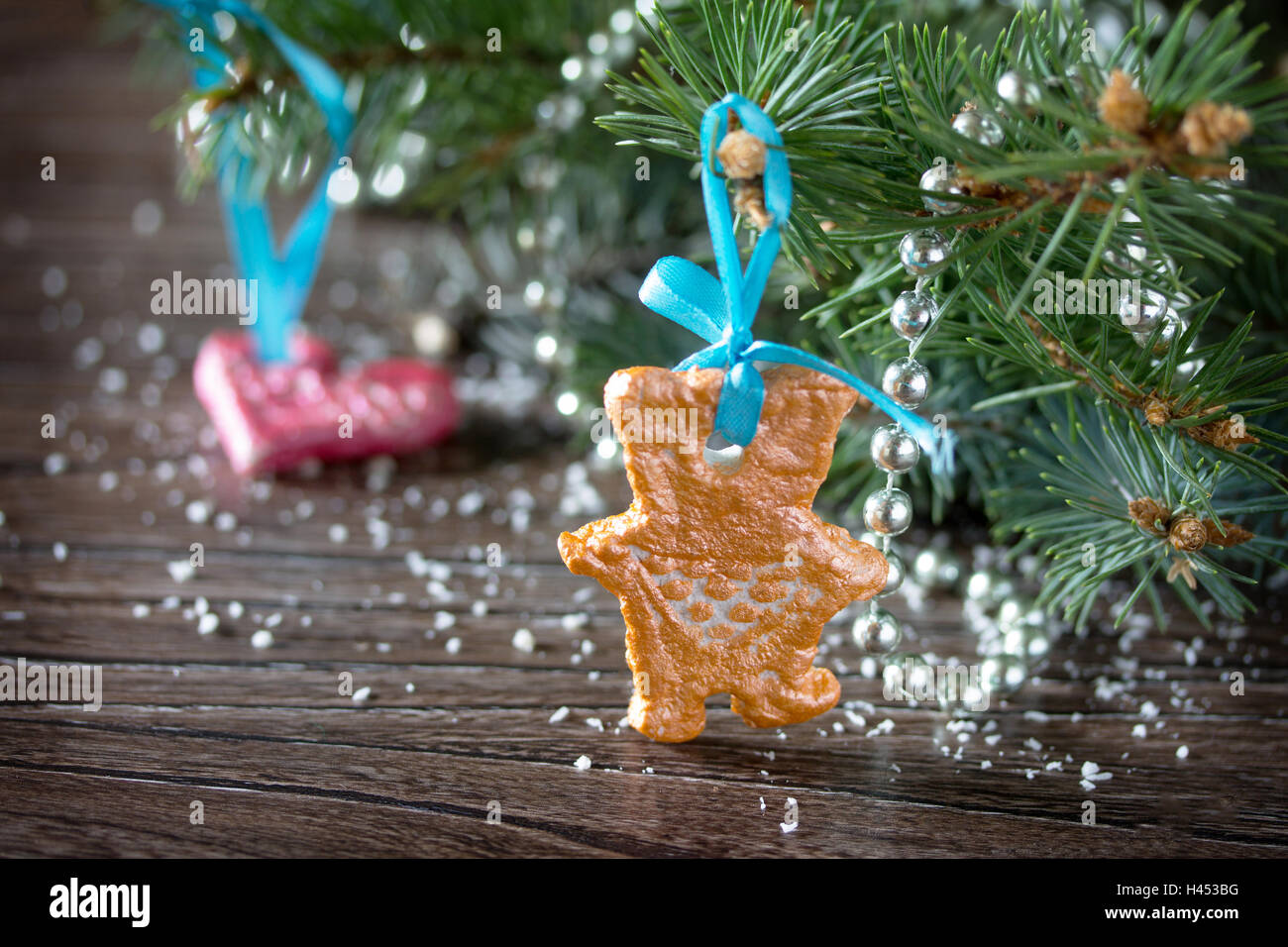 Christmas tree branches and Christmas toys made of of salt dough on wooden background. Stock Photo