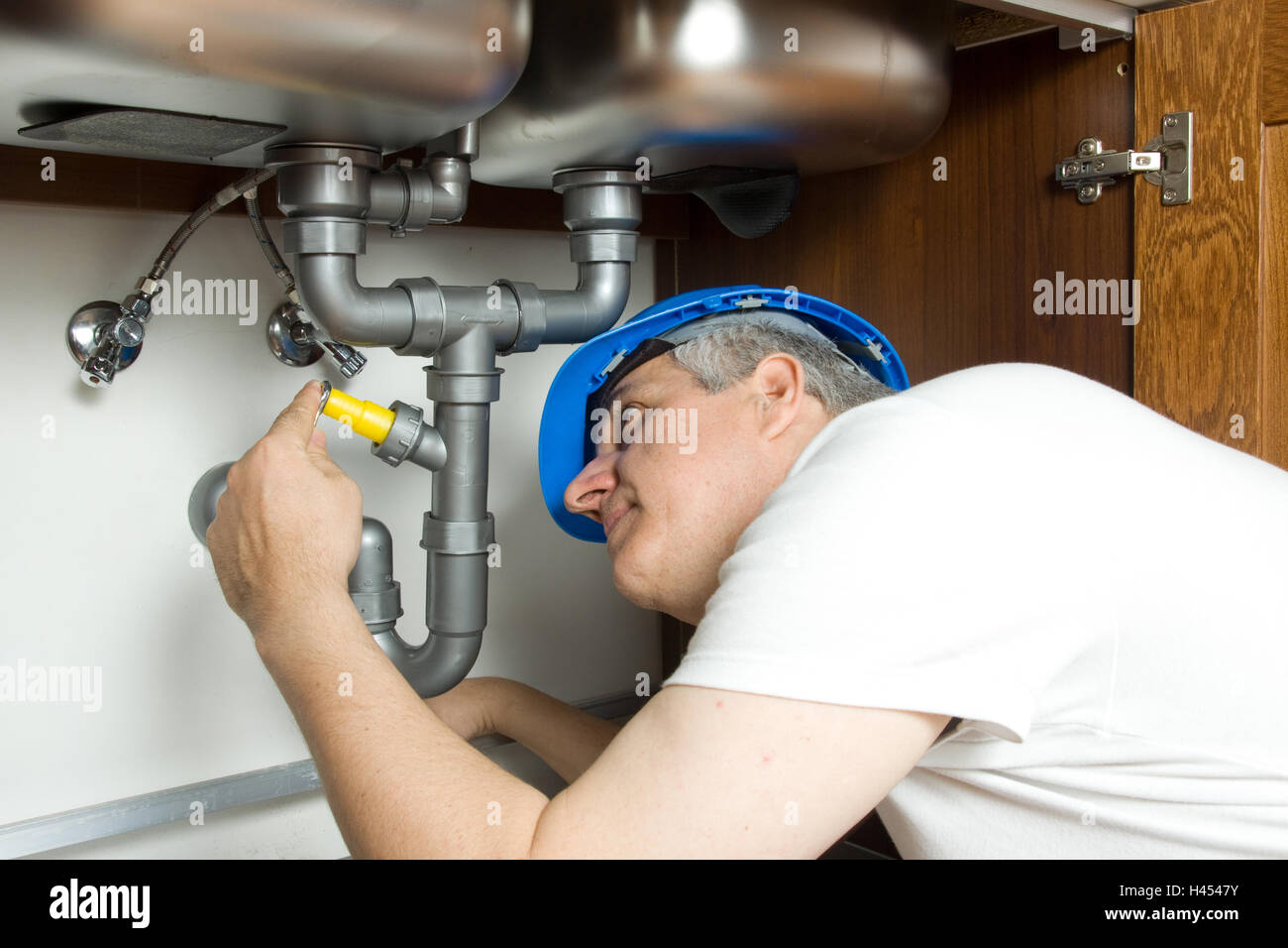plumber at work in a kitchen fixing a sink - Stock Image