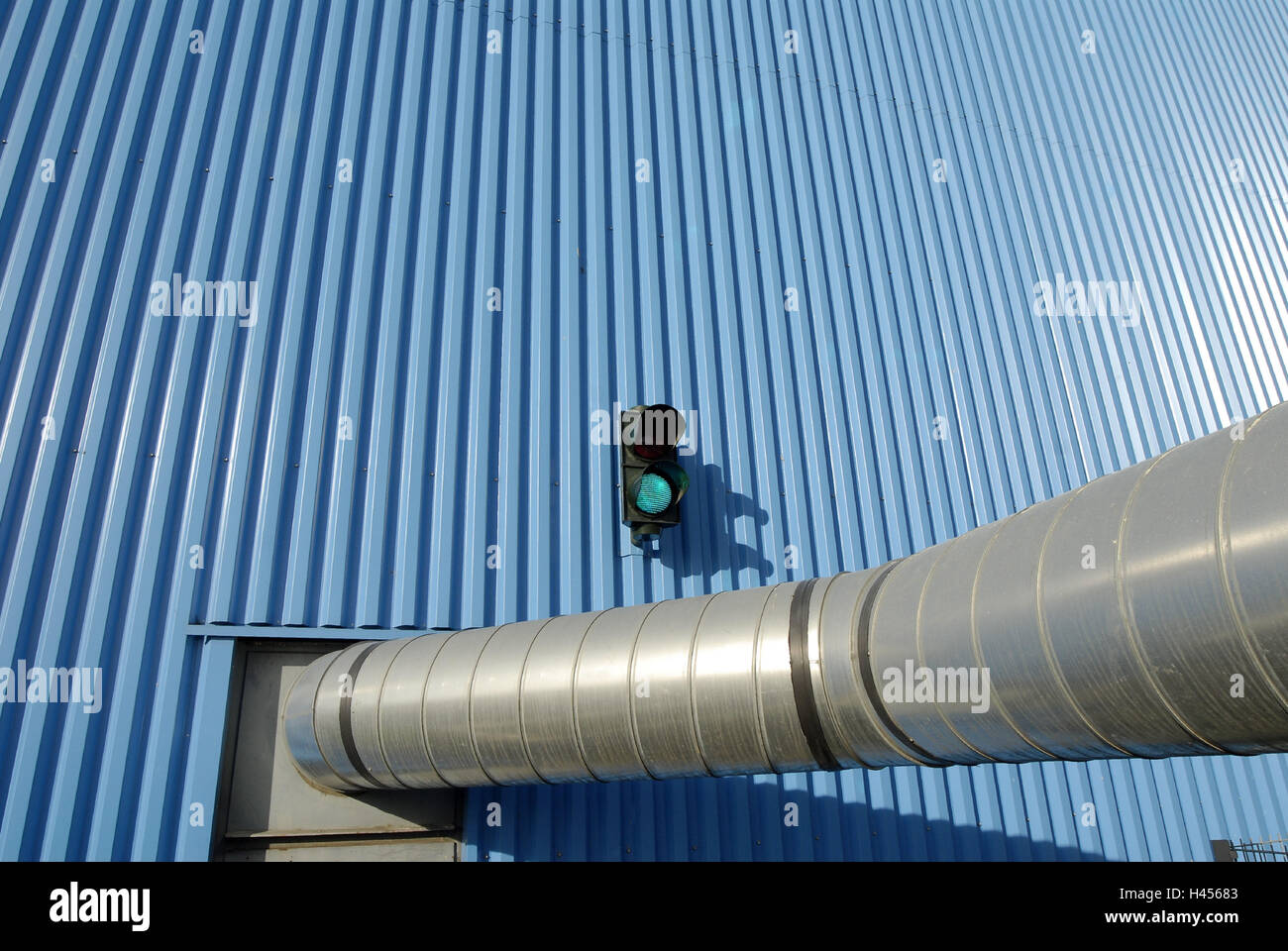Industrial building, corrugated iron facade, ventilation pipe, traffic light, - Stock Image