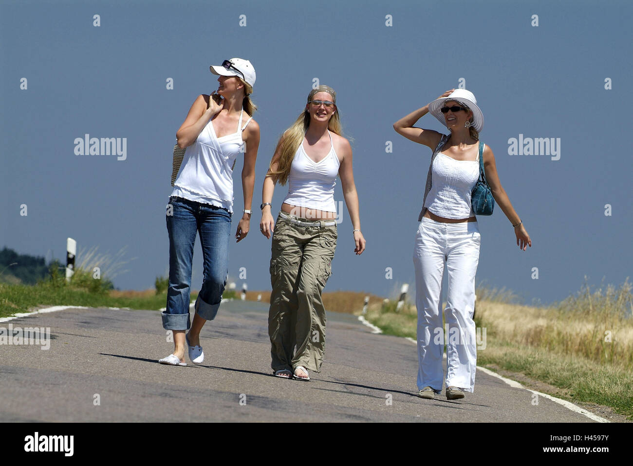 Women, three, young, country road, goes, cheerfully, summers, - Stock Image