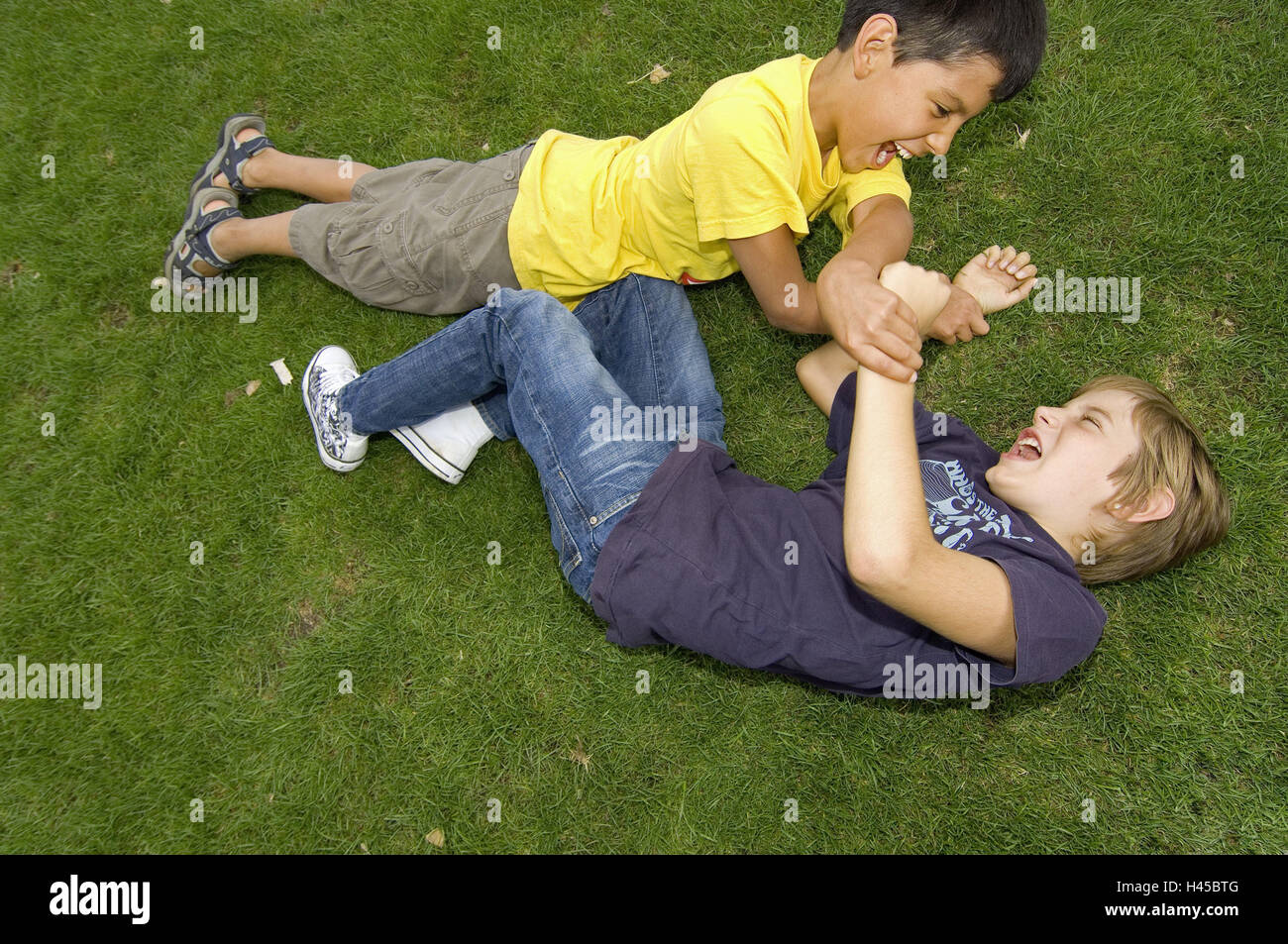 Boys, two, turfs, lie, scuffle, model released, people, children, friends, outside, meadow, park, fight, fight, - Stock Image