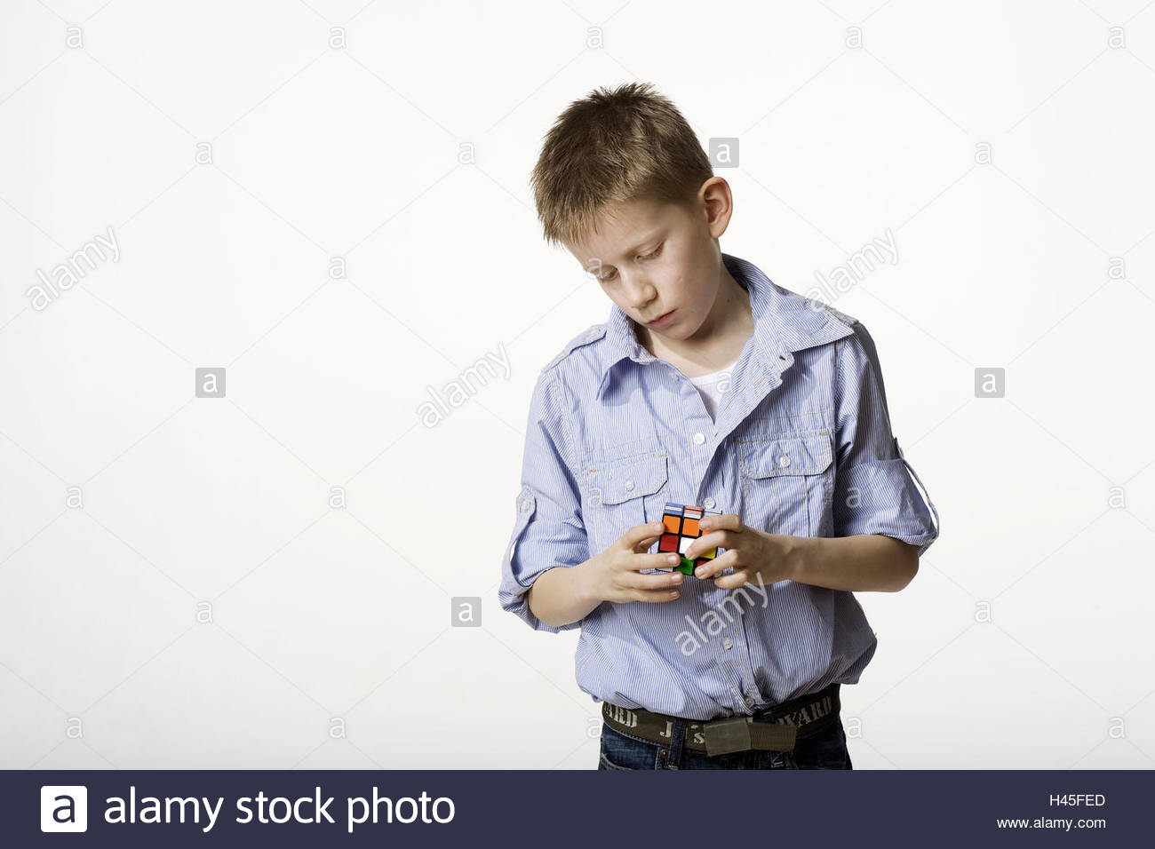 Boy, stand, magic cubes, rotate, play, half portrait, model released, no property release, studio, cut out, person, - Stock Image