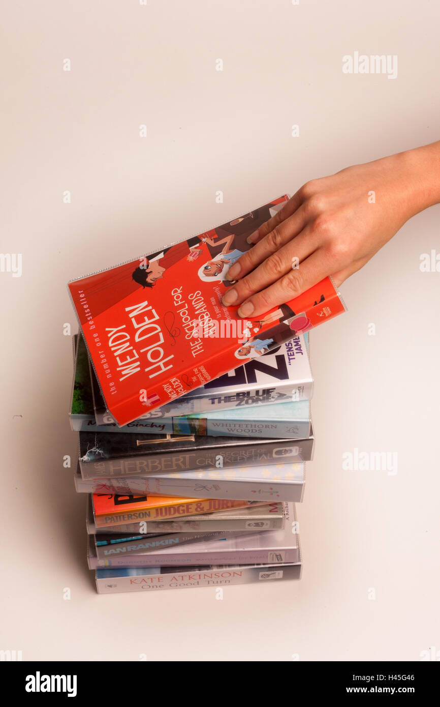 A stack of books on a plain background. - Stock Image